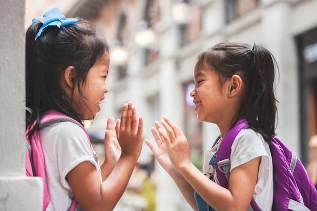 Dos muchachas asiáticas lindas del niño con el bolso de escuela que juegan junto después de escuela en la escuela