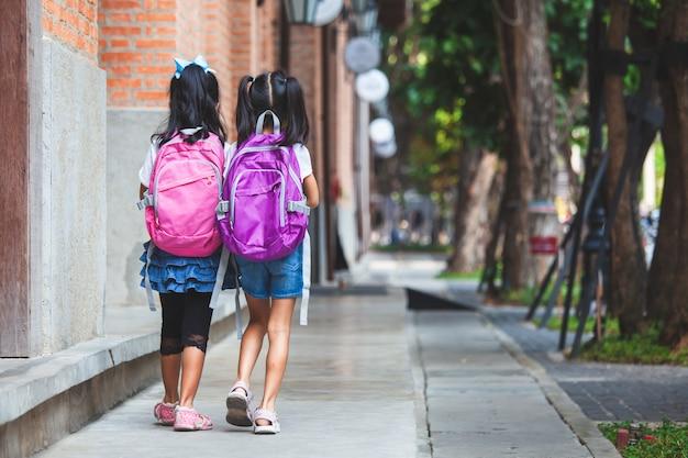 Dos muchachas asiáticas lindas del niño con el bolso de escuela que lleva a cabo la mano y caminan juntas en la escuela