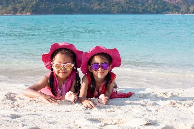 Dos muchachas asiáticas lindas del niño que llevan el sombrero rosado y las gafas de sol que juegan con la arena junta en la playa