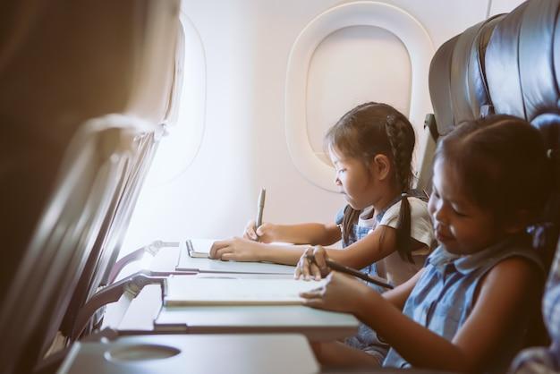 Dos muchachas asiáticas lindas del niño que viajan en un aeroplano y que pasan el tiempo dibujando y leyendo