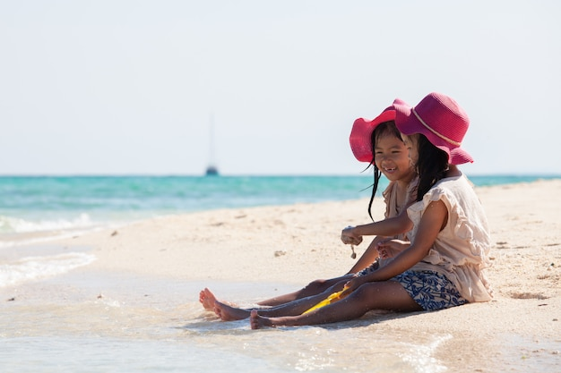 Dos muchachas asiáticas lindas del pequeño niño que se sientan y que juegan con la arena juntas en la playa