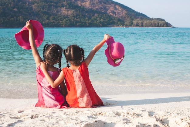 Dos muchachas asiáticas lindas del pequeño niño que sostienen el sombrero que se sienta y que juega junto en la playa