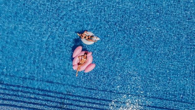 Dos muchachas hermosas jóvenes felices con hermosas figuras nadan