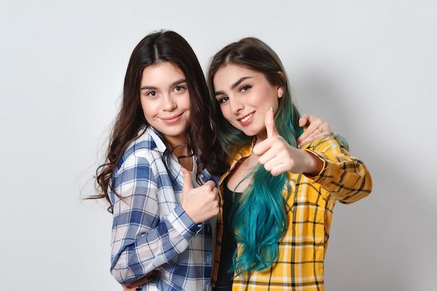 Dos muchachas hermosas que sonríen y que muestran los pulgares para arriba. en la pared blanca