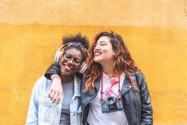 Dos muchachas latinas adolescentes que se unen sobre una pared amarilla.