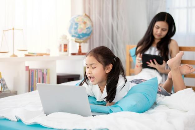 Dos muchachas lindas del niño asiático que usan la tableta y la computadora portátil en cama.