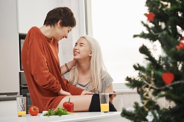 Dos muchachas lindas que se sientan en cocina mientras que habla y ríe durante el desayuno cerca del árbol de navidad. típica mañana feliz de novias tiernas en relación que viven juntas