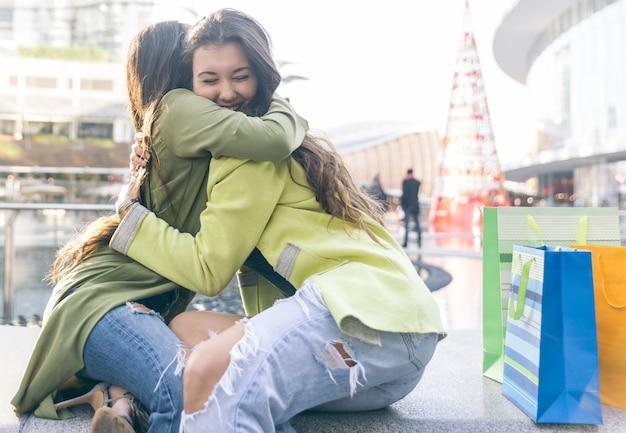Dos muchachas que se abrazan después de mucho tiempo de haber estado distantes