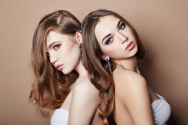 Dos muchachas rubias jovenes atractivas de la moda que abrazan maquillaje