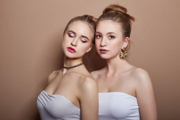 Dos muchachas rubias jovenes atractivas de la moda que abrazan