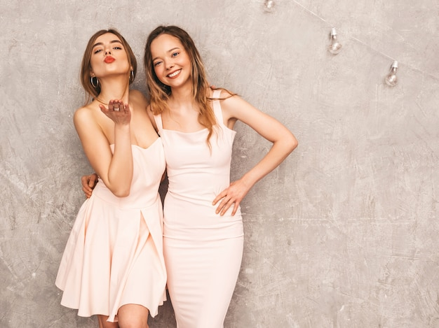 Dos muchachas sonrientes hermosas jovenes en vestidos rosados claros de moda del verano. sexy mujer despreocupada posando. modelos positivos divirtiéndose. dar beso