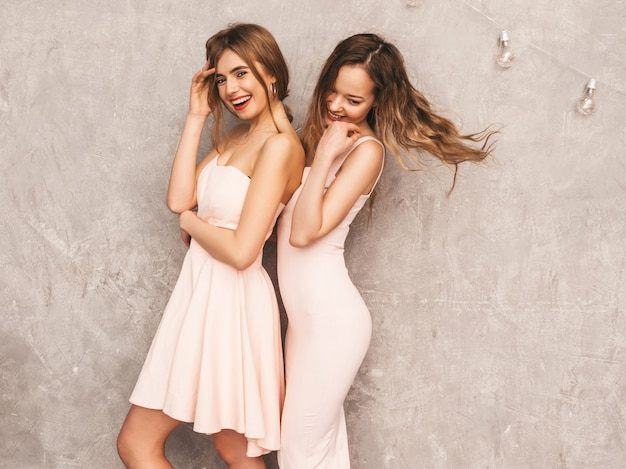 Dos muchachas sonrientes hermosas jovenes en vestidos rosados claros de moda del verano. sexy mujer despreocupada posando. modelos positivos divirtiéndose
