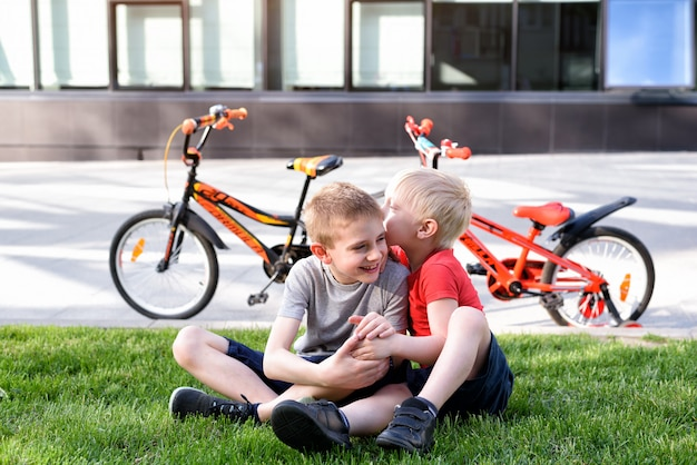 Dos muchachos se comunican sentados en el césped. descanse después de andar en bicicleta, bicicletas en el fondo
