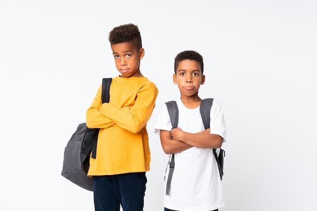 Dos muchachos estudiantes afroamericanos sobre blanco aislado