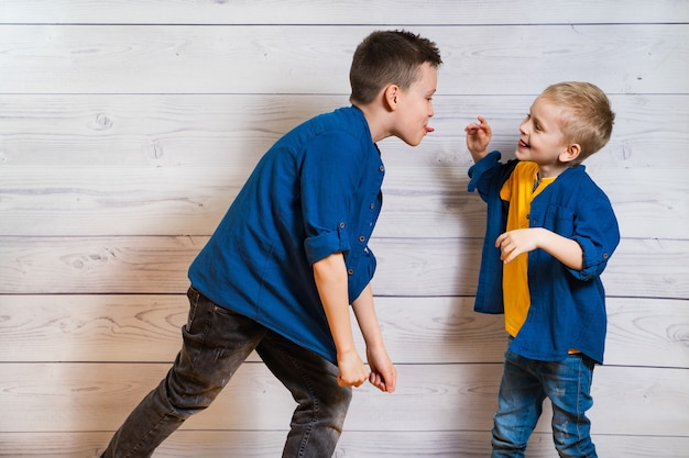 Dos muchachos en ropa casual en madera blanca mostrando lenguas el uno al otro