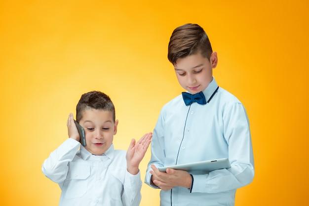 Los dos muchachos usando la computadora portátil en la pared naranja