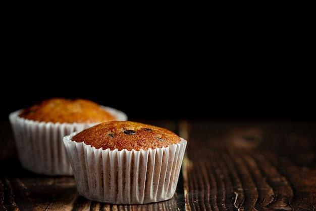 Dos muffins de chocolate puestos sobre un piso de madera