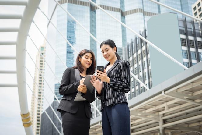 Dos mujer de negocios de pie usando smartphone y discutir delante de la oficina. concepto de trabajo de negocios.