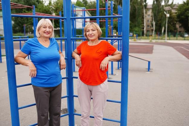 Dos mujeres adultas haciendo ejercicios al aire libre en el estadio