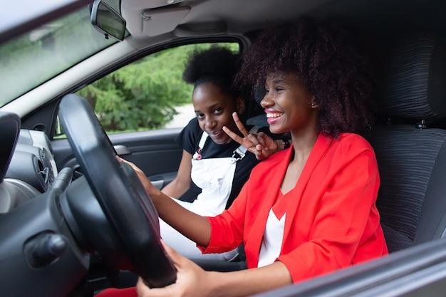Las dos mujeres afroamericanas divirtiéndose en el coche