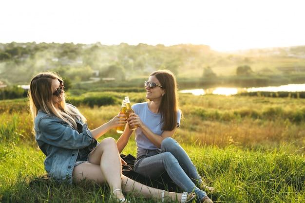 Dos mujeres alegres y jóvenes amigos con gafas de sol, bebiendo cerveza y disfrutando del tiempo que pasaron juntos al atardecer.