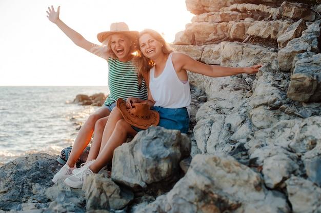 Dos mujeres alegres jóvenes en sombreros de hipsters en roca en la costa del mar. paisaje de verano con chica, mar, islas y luz solar naranja.