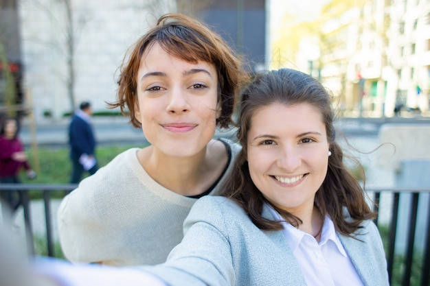 Dos mujeres alegres posando para autorretrato