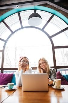 Dos mujeres alegres sentado y usando laptop en café