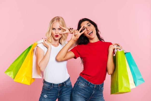 Dos mujeres alegres sosteniendo paquetes en los hombros y mostrando gestos de paz mientras mira a la cámara sobre rosa