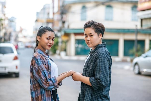 Dos mujeres amorosas de pie y cogidos de la mano en la calle.