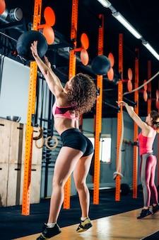 Dos mujeres arroja balones medicinales en el gimnasio