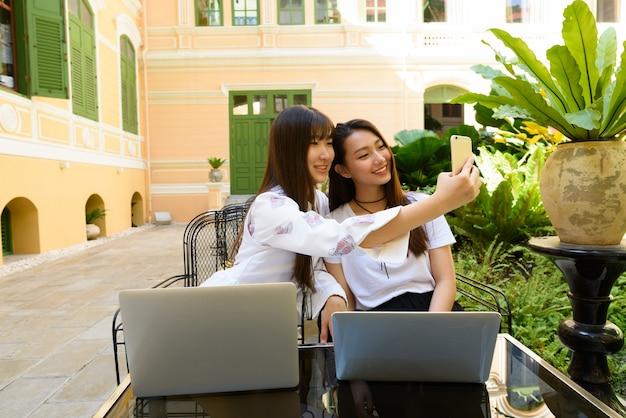 Dos mujeres asiáticas adolescentes jóvenes felices con laptop tomando selfie juntos en la cafetería.