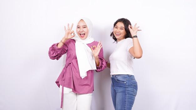 Dos mujeres asiáticas aprecian algo aislado superficie blanca