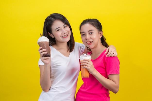 Dos mujeres asiáticas bebiendo té helado de leche y cacao helado en un amarillo.