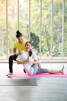 Dos mujeres asiáticas felices en posturas de yoga en estudio de yoga con escenario de luz natural / concepto de ejercicio / práctica de yoga / espacio de copia / estudio de yoga