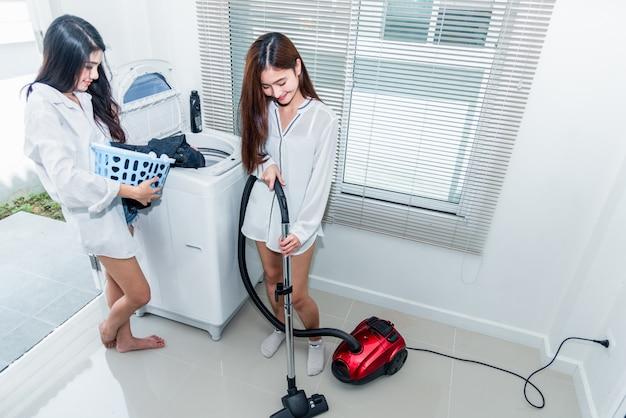 Dos mujeres asiáticas haciendo tareas domésticas y tareas en la cocina.