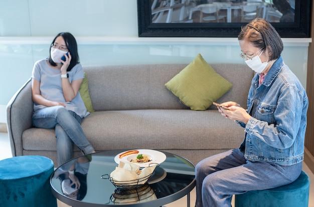 Dos mujeres asiáticas con mascarilla quirúrgica en un restaurante o cafetería