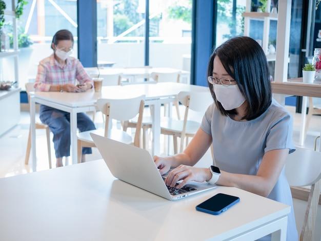 Dos mujeres asiáticas con mascarilla y usando un teléfono inteligente y una computadora portátil para realizar videollamadas o trabajar