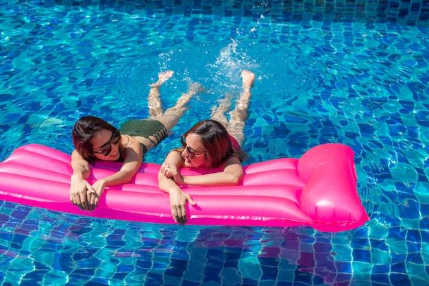 Dos mujeres asiáticas relajadas y tendidas en colchones inflables de color rosa.