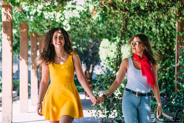 Dos mujeres atractivas jóvenes caminando en la ciudad