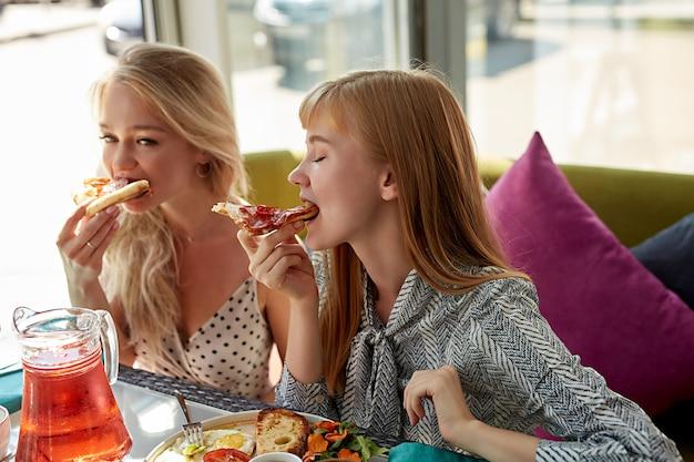 Dos mujeres atractivas jóvenes comen pizza sabrosa en el café