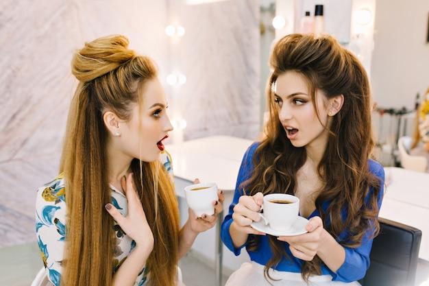 Dos mujeres atractivas sorprendidas asombradas hablando en un salón de belleza