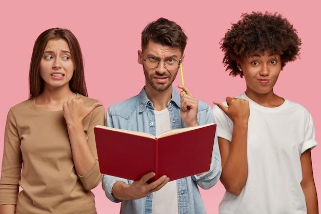 Dos mujeres avergonzadas de diferente raza señalan al chico desconcertado, sugieren hacerle esta pregunta ya que no saben la respuesta, se paran juntas contra la pared rosada. tema educativo