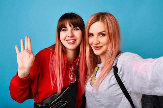 Dos mujeres bastante divertidas se juntan haciendo selfie, vistiendo sudaderas con capucha y gafas, pelos de moda rosa pastel, pared azul, sonriendo y saludando.