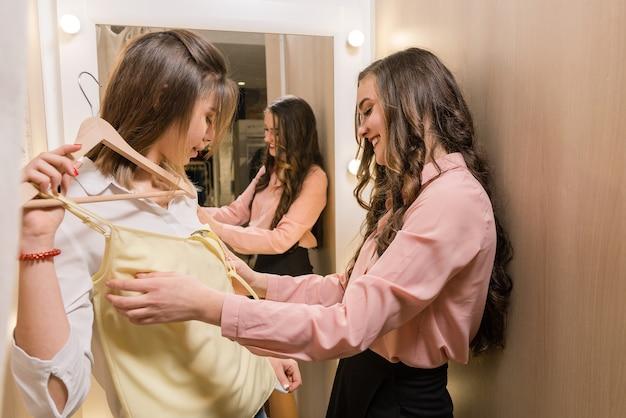 Dos mujeres bastante jóvenes alegres de pie en el probador y probándose ropa