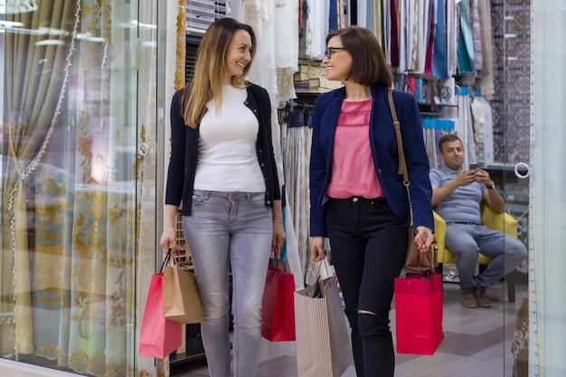 Dos mujeres con bolsas de compras en centro comercial
