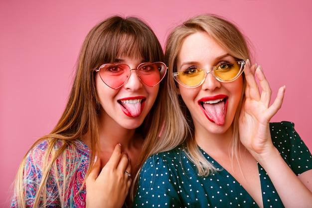 Dos mujeres bonitas divertidas que se divierten haciendo selfie y mostrando lenguas largas, vistiendo coloridos vestidos y gafas de sol, humor primavera verano, pared rosa.