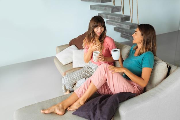 Dos mujeres bonitas hablando y bebiendo té, mientras está sentado en el sofá de la casa moderna