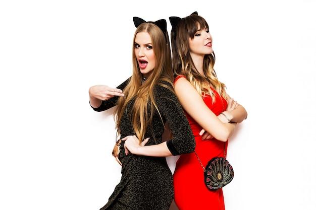 Dos mujeres bonitas en orejas de carnaval de gato