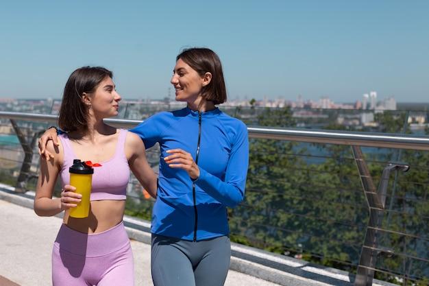 Dos mujeres bonitas en ropa deportiva en amigos del puente hablan felices y positivas mientras caminan sonríen, disfrutan de la mañana de fitness, increíbles vistas de la ciudad en el fondo